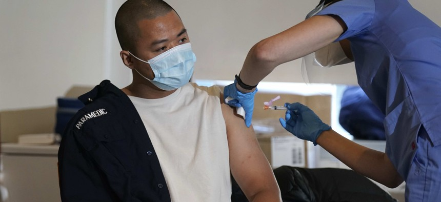 Medical personnel prepare a coronavirus vaccine against COVID-19 to be administered to New York City firefighter emergency medical services personnel at the FDNY Fire Academy in New York, Wednesday, Dec. 23, 2020.