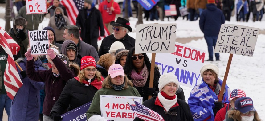 People attend a rally in support of President Donald Trump at the State Capitol in Lansing, Mich., Wednesday, Jan. 6, 2021.