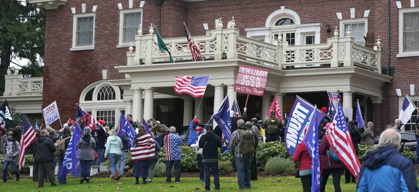 Protesters stand outside the Governor's Mansion after getting through a perimeter fence, Wednesday, Jan. 6, 2021, at the Capitol in Olympia, Wash.