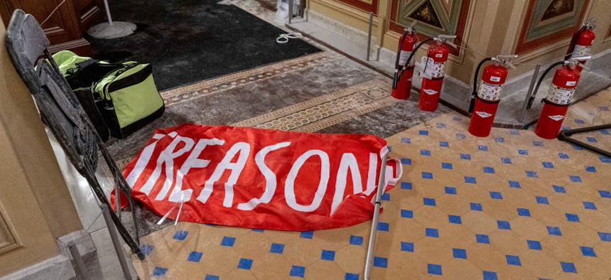 """A flag that reads """"Treason"""" is visible on the ground in the early morning hours of Thursday, Jan. 7, 2021."""