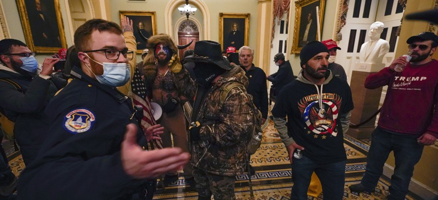 Protesters walk as U.S. Capitol Police officers watch in a hallway near the Senate chamber at the Capitol in Washington, Wednesday, Jan. 6, 2021.