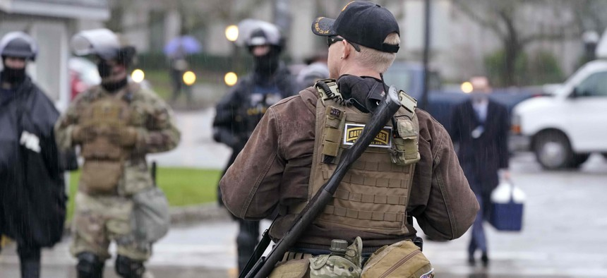 An armed protester stands outside the Capitol Monday, Jan. 11, 2021, in Olympia, Wash.