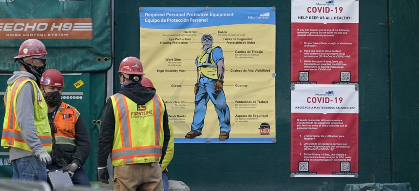 Construction workers wear masks as they stand next to posters with cautions about the spread of COVID-19, Thursday, Dec. 3, 2020.