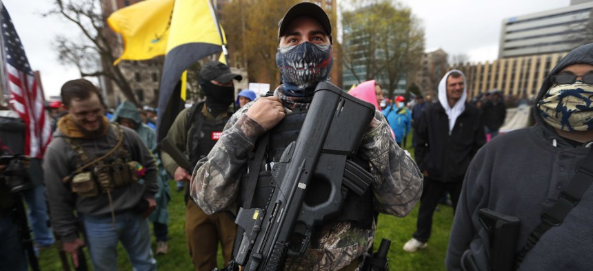 In this April 30, 2020, file photo, a protester carries his rifle at the State Capitol in Lansing, Mich.
