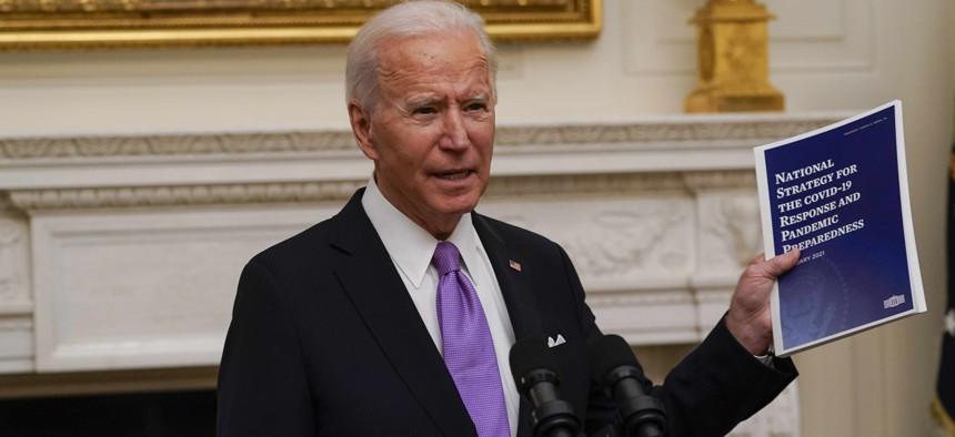 President Joe Biden holds a booklet as he speaks about the coronavirus in the State Dinning Room of the White House, Thursday, Jan. 21, 2021, in Washington.