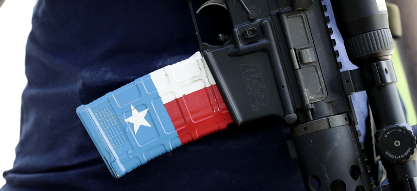 The ammo magazine is made to look like the Texas flag as gun rights advocates gather outside the Texas Capitol where Texas Gov. Greg Abbott held a round table discussion, Thursday, Aug. 22, 2019, in Austin, Texas.