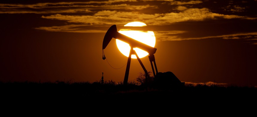 The sun sets behind an idle pump jack near Karnes City, Texas, during April 2020.