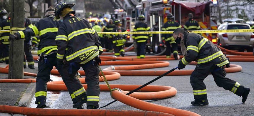 Firefighters work at the scene of a building fire in Englewood, N.J., on Dec. 2, 2020. Firefighters and other first responders are among the public workers unable to work remotely during the pandemic.