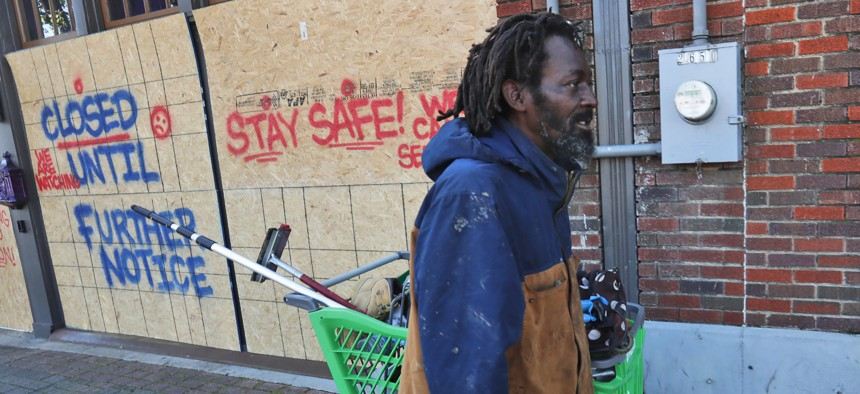 In this Tuesday, March 31, 2020 file photo, Vincent Amos, who identified himself as homeless, pulls a shopping cart with his belongings amid businesses closed by concerns of the COVID-19 coronavirus in the Deep Ellum section of Dallas.
