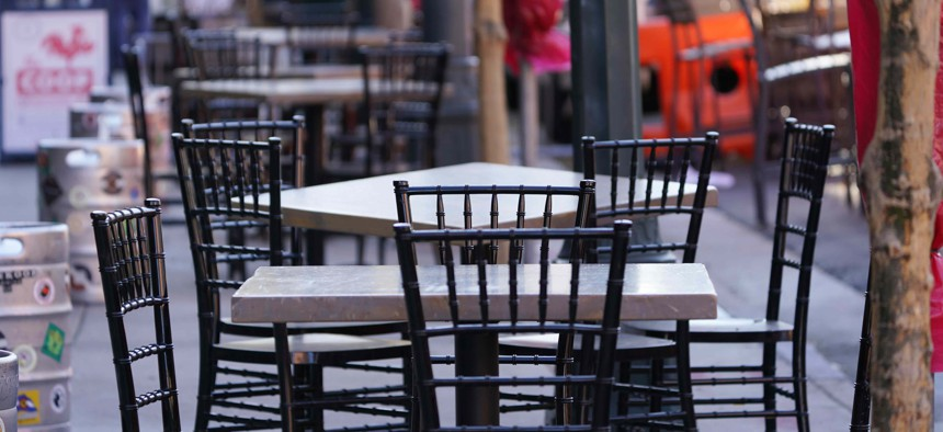Empty tables and chairs are set up outside a restaurant that offers outside dining to deal with the rapid spread of the new coronavirus, Thursday, Nov. 12, 2020, in downtown Denver.