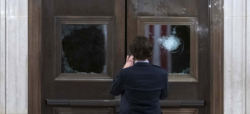 In this Jan. 7, 2021, file photo a man takes a photo of broken windows near the Rotunda in the early morning hours after insurrectionist loyal to President Donald Trump stormed the Capitol in Washington.
