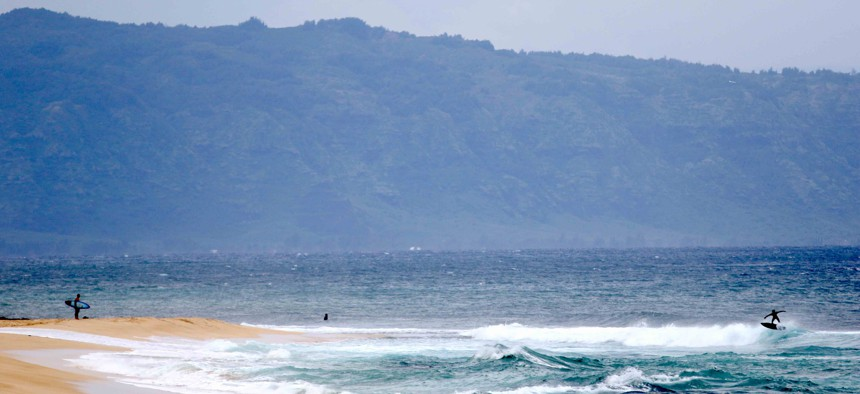 A surfer stands on the beach as another rides a wave on Oahu's North Shore near Haleiwa, Hawaii on Tuesday, March 31, 2020.