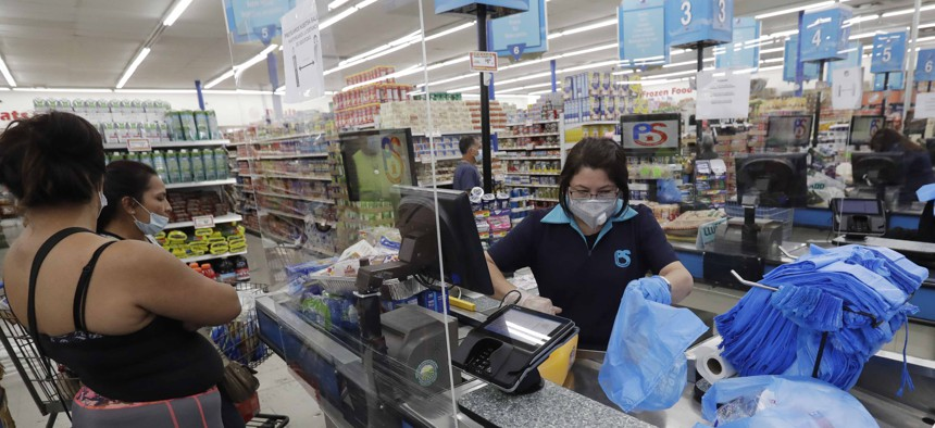 In this Wednesday, June 3, 2020 photo, a cashier bags groceries for customers at the Presidente Supermarket in the Little Havana neighborhood of Miami.