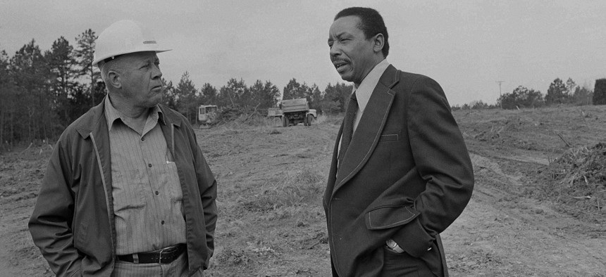 "Former civil rights lawyer-activist Floyd McKissick, right, talks to grade foreman A.T. Ayscue, in the empty fields where the future ""Soul City"" will be built in Warren County, N.C., June 20, 1974."