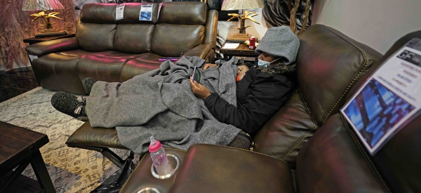 Natalie Harrell holds her sleeping daughter, Natasha Tripeaux while sitting in a recliner at a Gallery Furniture store after the owner opened his business as a shelter for those without power at homes Tuesday, Feb. 16, 2021, in Houston.