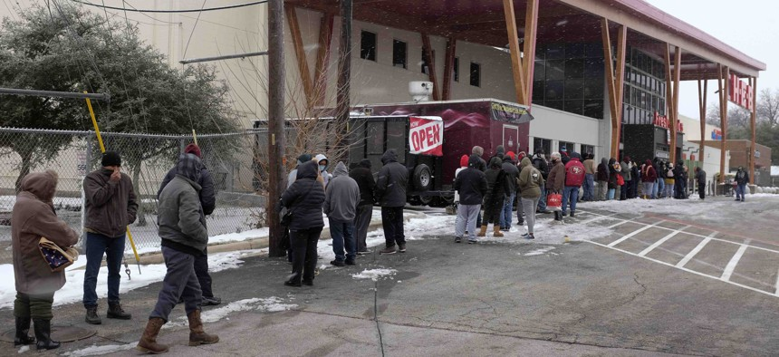 People stand in line outside an HEB grocery store in the snow Thursday, Feb. 18, 2021, in Austin, Texas. The store did not have milk, eggs, meat or refrigerated items.