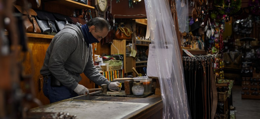 Leather artisan Armando Murillo works in his shop on Olvera Street in downtown Los Angeles, Wednesday, Dec. 16, 2020. Olvera Street, known as the birthplace of Los Angeles, has been particularly hard hit by the coronavirus pandemic.