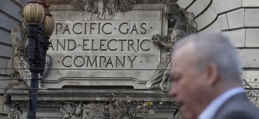 In this Dec. 16, 2019, file photo, is a man walking past a Pacific Gas and Electric sign on a PG&E building in San Francisco.