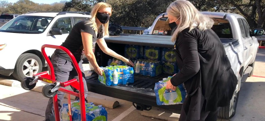 Austin City Council Member Paige Ellis, left, used her fiance's truck to distribute water to constituents during severe winter storms in Texas.