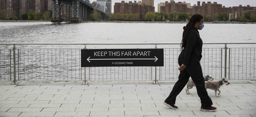 A dog walker passes a social distancing sign while wearing a protective mask at Domino Park, Friday, May 8, 2020, in the Brooklyn borough of New York.