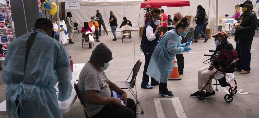 People who are homeless wait to get Covid-19 vaccine shots at a vaccination site set up in the parking lot of the Los Angeles Mission in the Skid Row area of Los Angeles, Wednesday, Feb. 10, 2021.