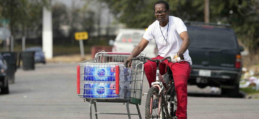 A Fifth Ward resident pulls a shopping cart with donated water back to her home Friday, Feb. 26, 2021, in Houston.