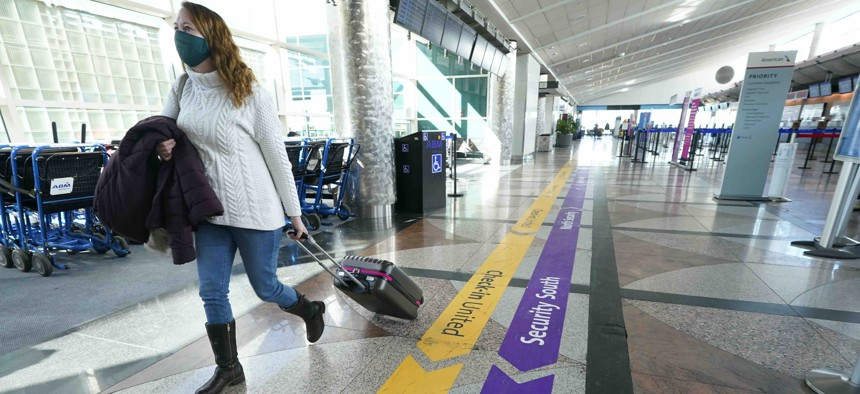 A lone traveler wears a face covering while in the main terminal of Denver International Airport