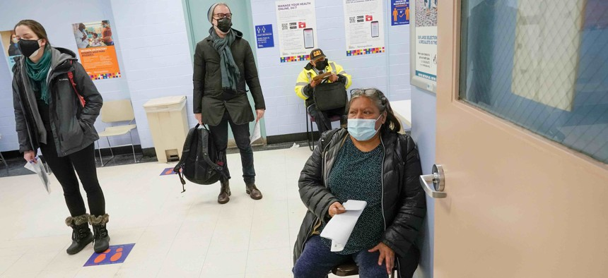 Maria Hernandez, right, of Manhattan, sits in a waiting area after registering for the first dose of the coronavirus vaccine at a COVID-19 vaccination site at NYC Health + Hospitals Metropolitan, Thursday, Feb. 18, 2021, in New York.