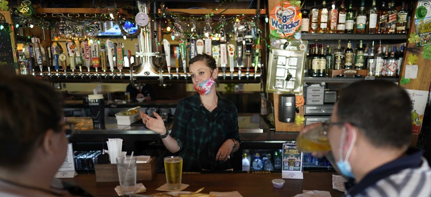 Bartender Alyssa Dooley, center, talks with customers at Mo's Irish Pub, Tuesday, March 2, 2021, in Houston. Texas Gov. Greg Abbott announced that he is lifting business capacity limits and the state's mask mandate starting next week.