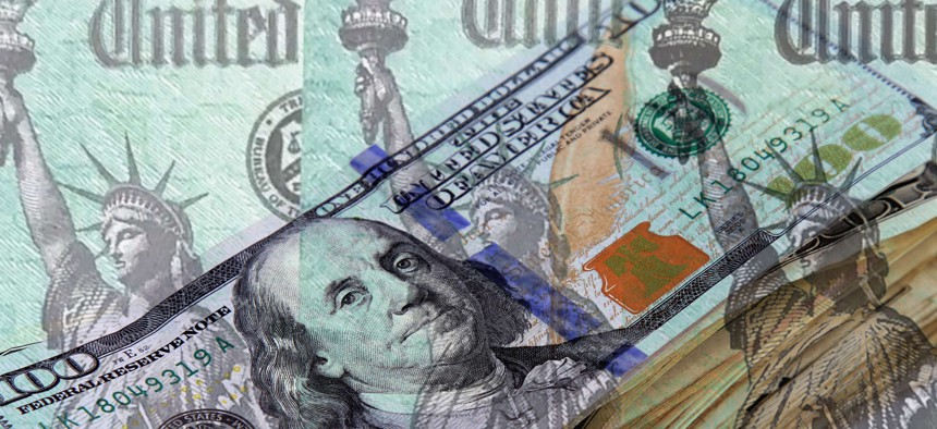 Row of Federal treasury checks over background of a stack of US currency.