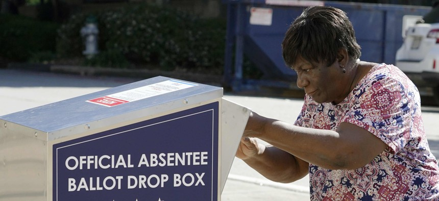 A voter drops their ballot off during early voting in Athens, Ga.