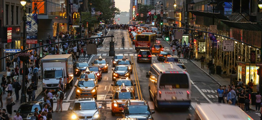 Commuters crossing busy 42nd Street in New York City, USA in afternoon.