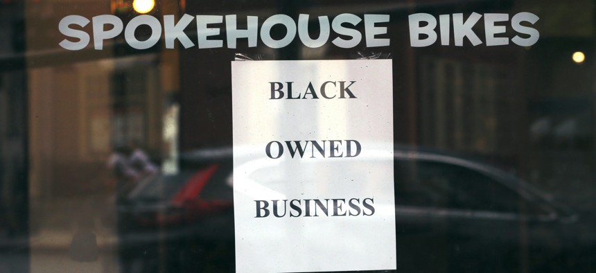 A sign in the window informs passersby that Spokehouse Bikes in the Upham's Corner neighborhood of Boston is a Black-owned business.