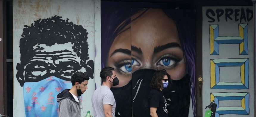 Pedestrians wearing masks to protect against the spread on COVID-19 pass murals painted on a boarded-up business in downtown Austin, Texas