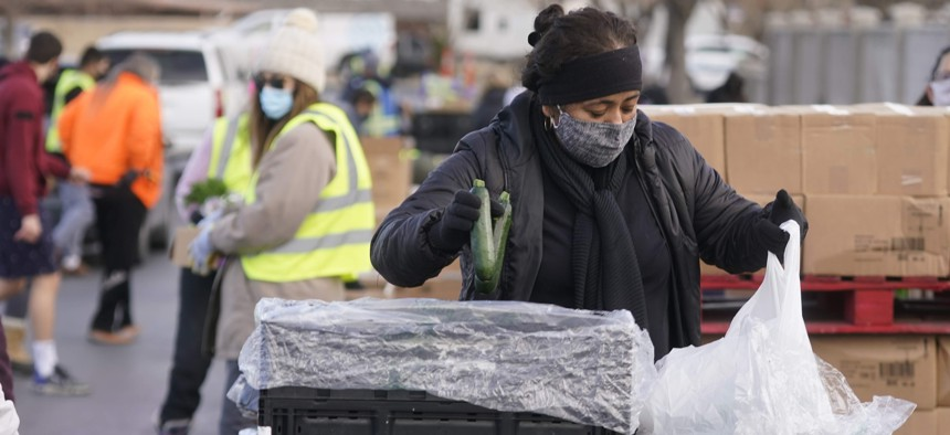 A volunteer carries food to waiting cars at the Utah Food Bank's mobile food pantry Thursday, March 11, 2021, in West Valley City, Utah.