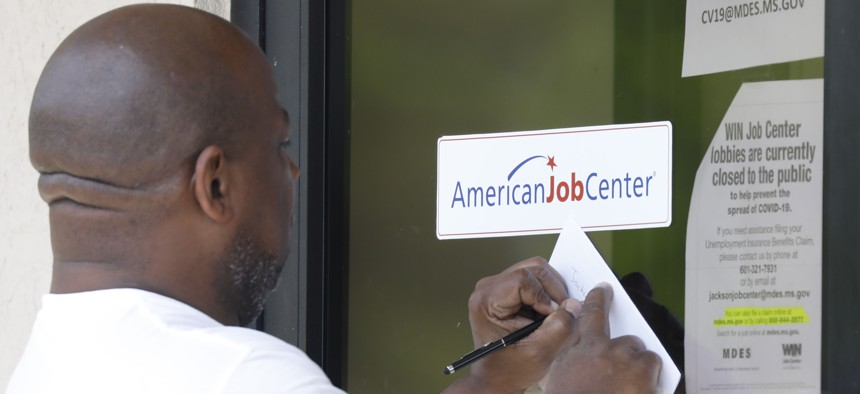 A resident copies down the Mississippi unemployment benefit website after being unable to enter the state WIN Job Center in north Jackson, Miss.