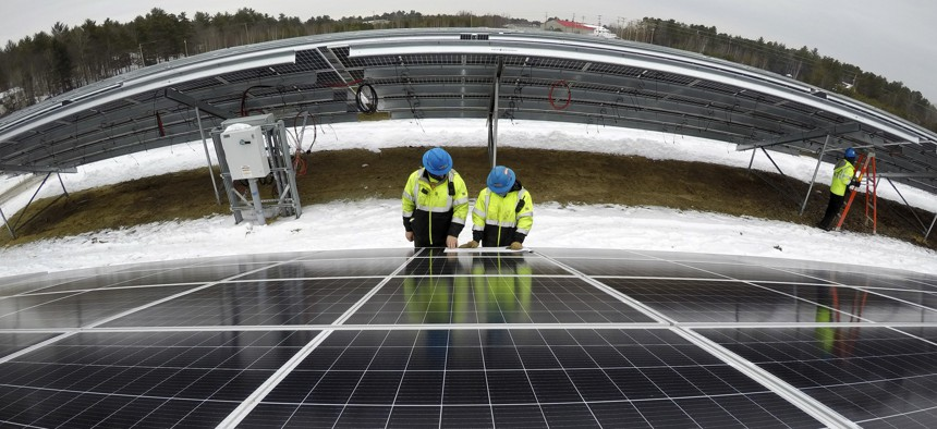 Electricians Bryan Driscoll and Zach Newton and consult a wiring schematic while installing solar panels at the 38-acre BNRG/Dirigo solar farm, Thursday, Jan. 14, 2021, in Oxford, Maine.
