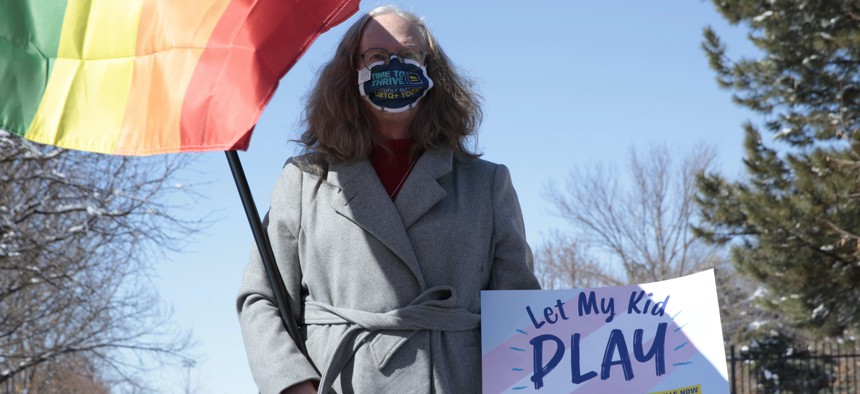 A parent demonstrates against a proposed ban on transgender girls and women from female sports leagues outside the South Dakota governor's mansion in Pierre, S.D.