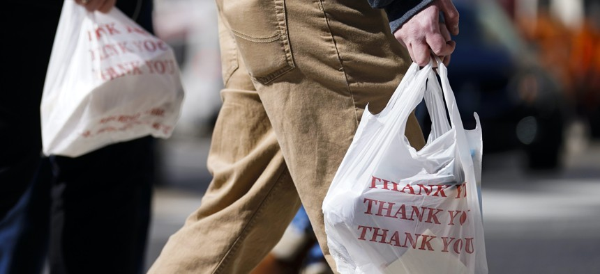 Pedestrians carry plastic bags in Philadelphia, Wednesday, March 3, 2021. Philadelphia and three other municipalities in Pennsylvania sued the state Wednesday over what they say was a covert abuse of legislative power to temporarily halt local bans or tax