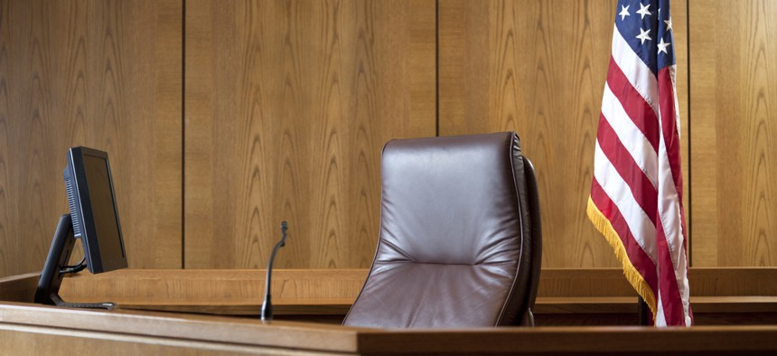 Courtroom bench in a wood panneled courtroom.