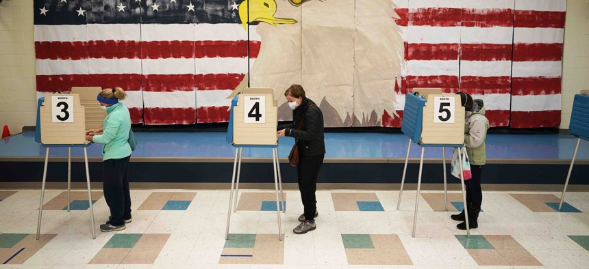 Voters cast their ballots under a giant mural at Robious Elementary school on Election Day, in Midlothian, Va., Tuesday Nov. 3, 2020.