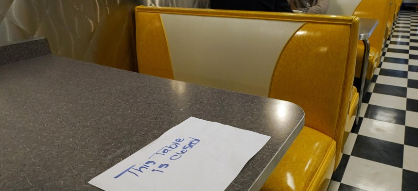 In this Nov. 17, 2020, file photo, a closed sign is posted on this table notifying diners in keeping with social distancing guidelines at Linda's Soda Bar and Grill in the Sutter County community of Yuba City, Calif.