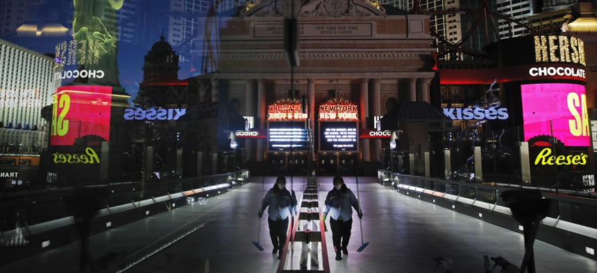 In this April 18, 2020, file photo, a lone worker wearing a mask cleans a pedestrian walkway devoid of the usual crowds as casinos and other business are shuttered due to the coronavirus outbreak in Las Vegas.