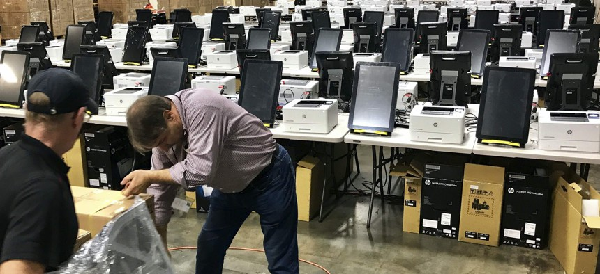 Photo shows voting equipment including touchscreen tablet, printer and scanner in a metro Atlanta warehouse, to be tested before shipped to Georgia counties. With early voting already underway, the Athens-Clarke County Board of Elections voted 3-2.