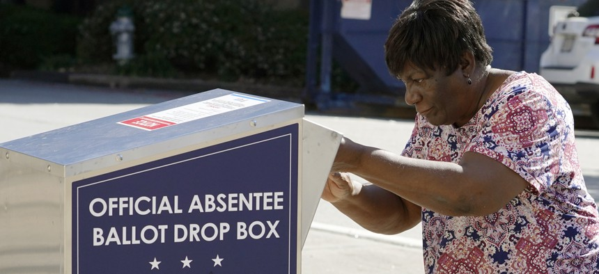 In this Oct. 19, 2020 file photo, a voter drops their ballot off during early voting in Athens, Ga.