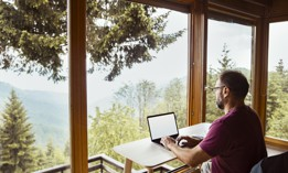 A man works remotely from his cabin in the woods.