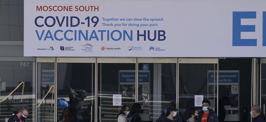 People walk outside a COVID-19 vaccination site at Moscone Center South during the coronavirus pandemic in San Francisco.