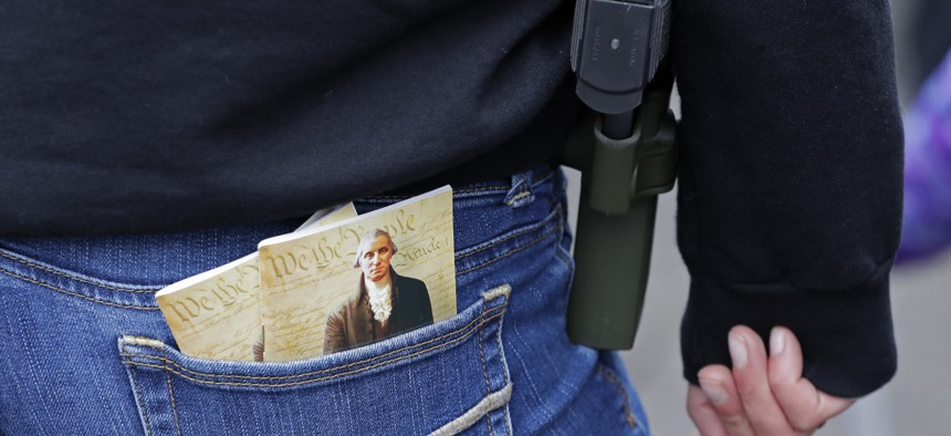 In this Jan. 12, 2018 photo, a woman wears a gun in a holster next to two copies of the U.S. Constitution during a gun rights rally at the Capitol in Olympia, Wash.