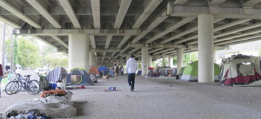 Individuals walk around a homeless encampment near downtown Houston, Texas.