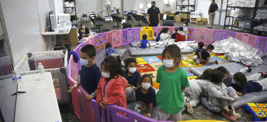 Young unaccompanied migrants, from ages 3 to 9, watch television inside a playpen at the U.S. Customs and Border Protection facility, the main detention center for unaccompanied children in the Rio Grande Valley, in Donna, Texas.